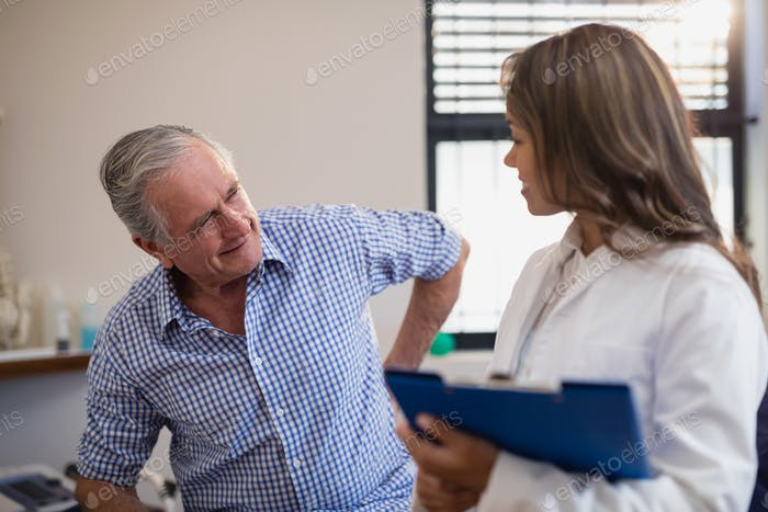 Senior male patient showing back ache to female doctor with file