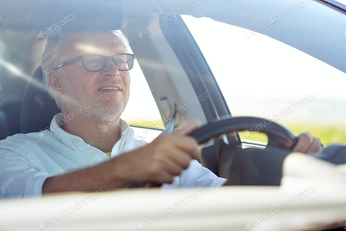 happy senior man in glasses driving car
