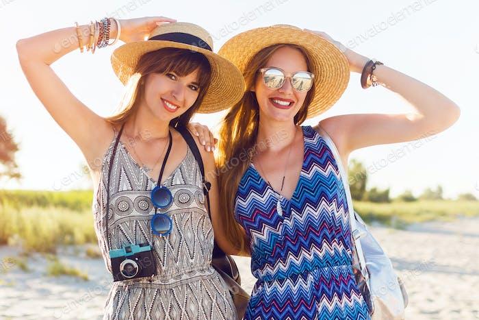 Disparo al aire libre de jóvenes amigas alegres juntas en una playa al atardecer