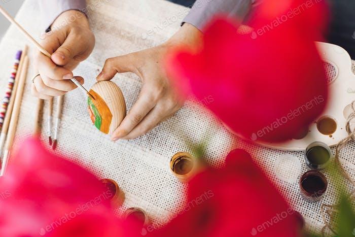 Руки держат и роспись пасхальное яйцо на деревенском столе с краской, кисти, тюльпанами