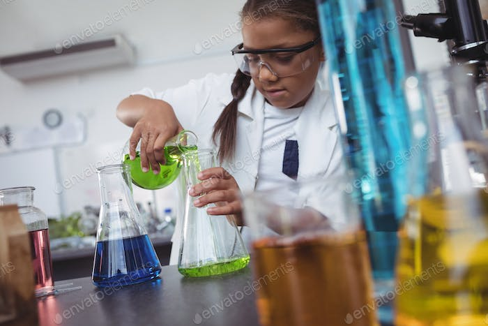 Elementary student pouring green chemical in flask at laboratory