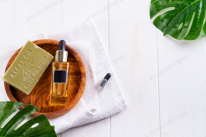 Cosmetic bottle with serum or hyaluronic acid and olive soap on wooden plate , palm leaf, on a white