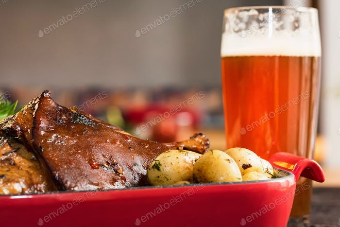 Close up roast pork knuckle served with boiled potatoes and glass of beer
