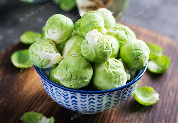 Fresh organic brussels sprouts in a bowl on a dark background. Healthy food. Vegan/vegetarian meal.