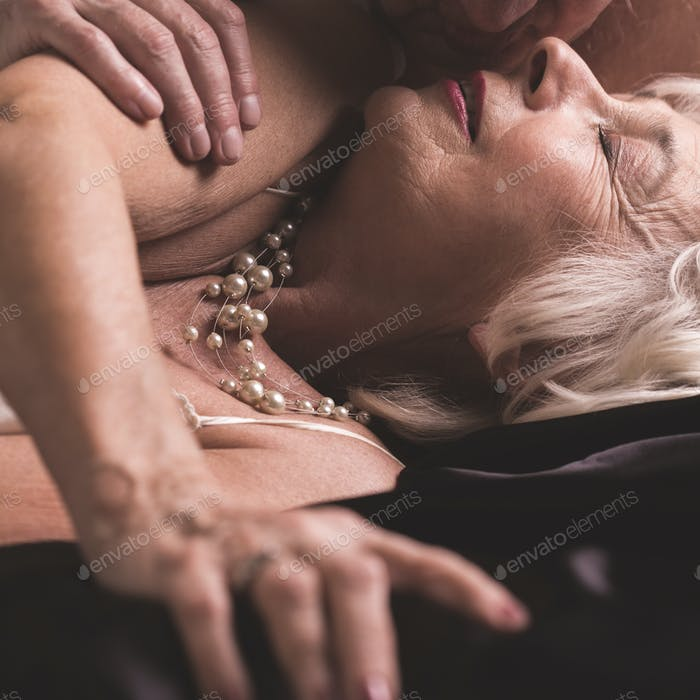 Elderly couple kissing during foreplay
