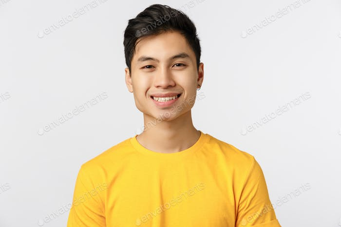 Close-up cheerful enthusiastic asian man with pierced ear, wear yellow t-shirt, smiling beaming grin