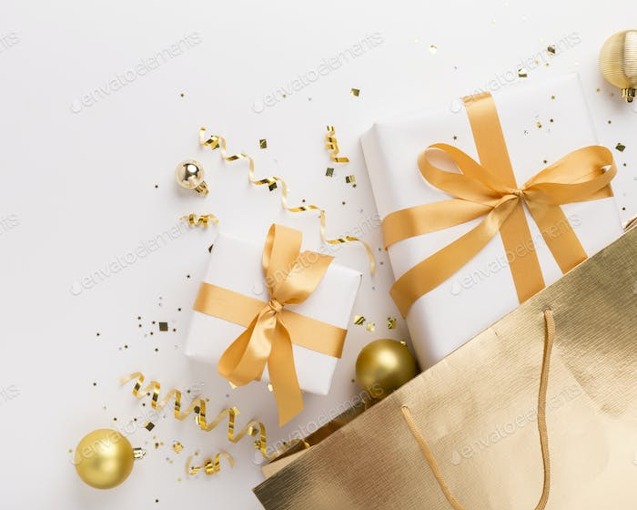 Christmas presents in gold bag with confetti on white