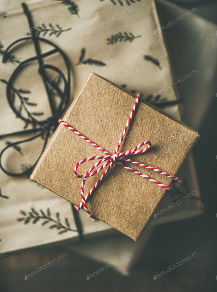 Flat-lay of gift boxes, rope, scissors over rustic wooden table