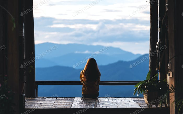 a female traveler sitting and looking at a beautiful mountain and nature view before sunset