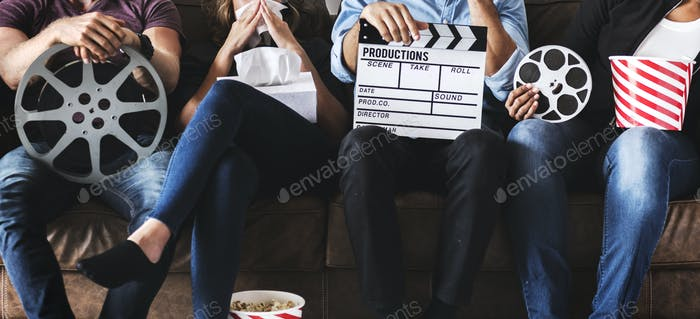 Group of friends holding movie and film objects