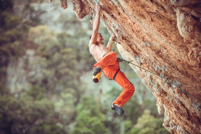 Junger Kletterer nach Springen und Greifen kleiner Handgriffe auf überhängenden Klippen