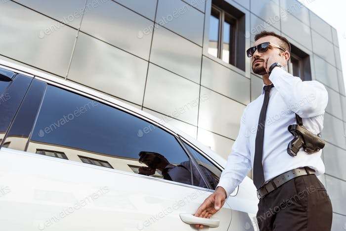 low angle view of handsome security guard listening message with security earpiece near car