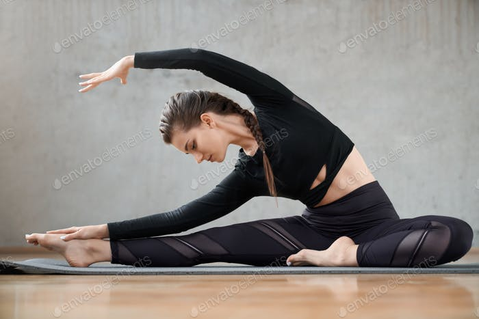Fit woman practicing yoga side bending exrcise