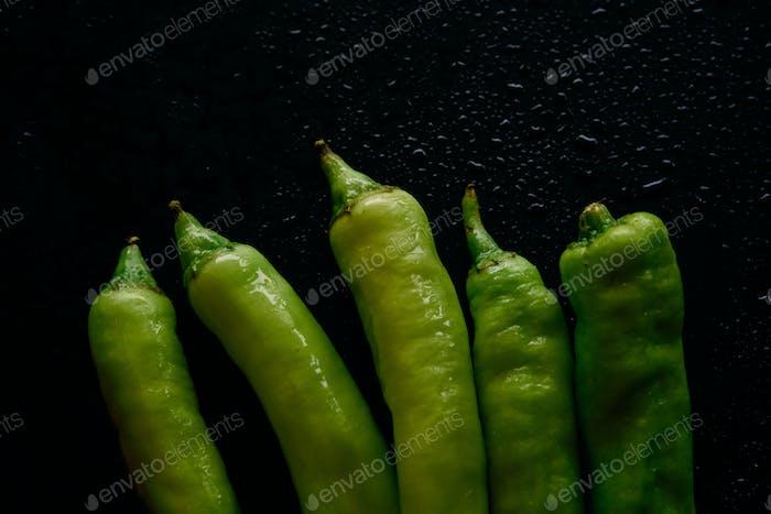 Green chili pepper on black floor