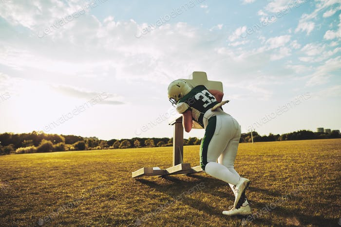 American football player practicing with a tackle sled outside