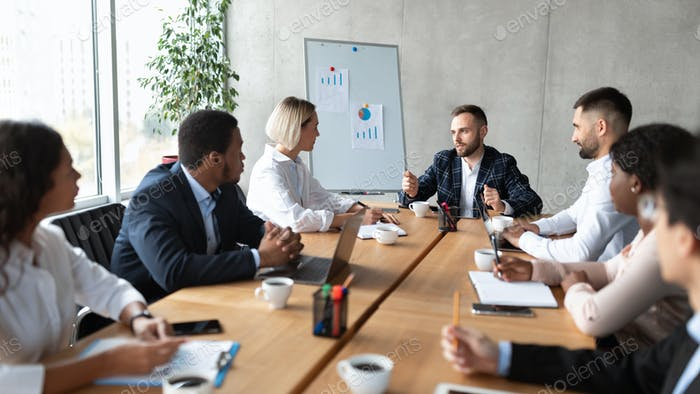 Multiracial Colleagues At Corporate Meeting Sitting At Desk In Office