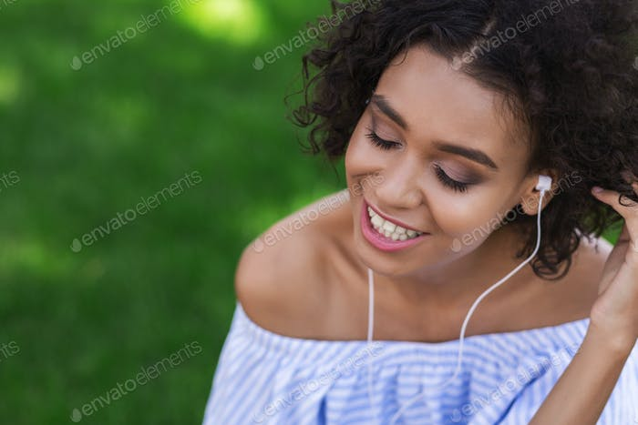 Happy african-american girl listening music in park