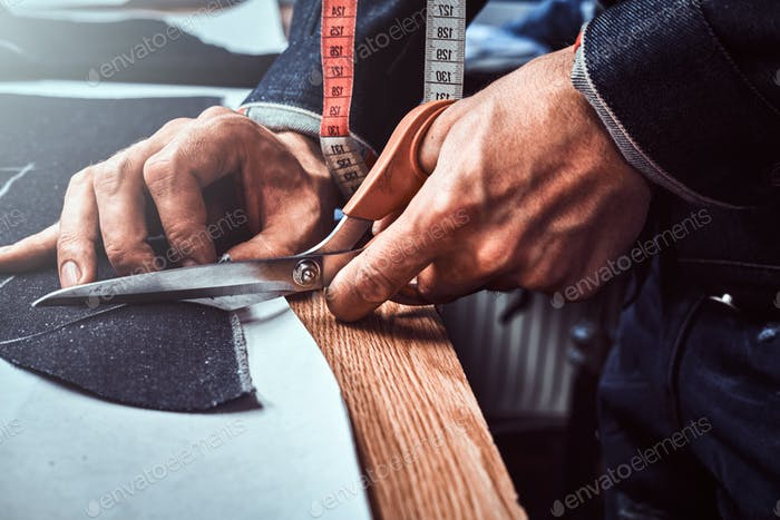 Modedesigner schneidet Stoff mit einer Schere ab.