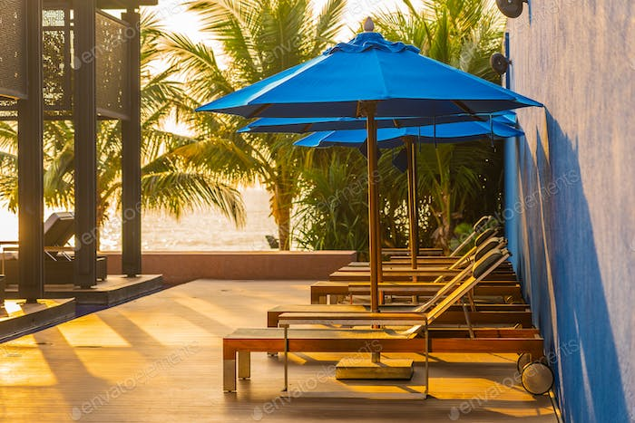 Empty chair and umbrella around swimming pool in hotel and resor