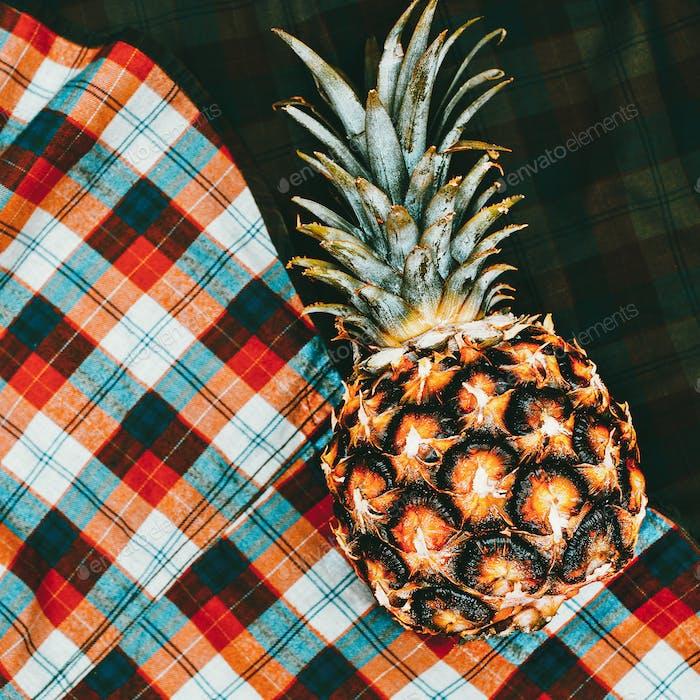 Ananas auf einem karierten Hemdhintergrund. Minimale Kunst