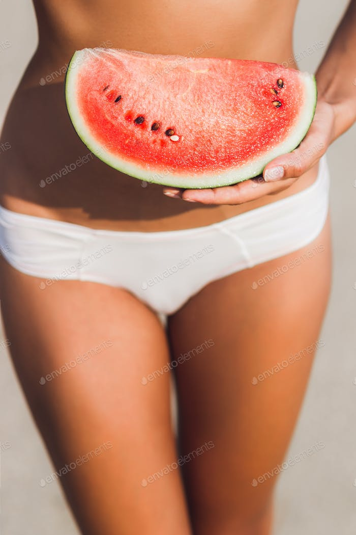 Girl holding a piece of watermelon in hands
