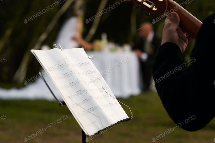 Cropped image of a musician and a rack with notes against a pair of newlyweds.
