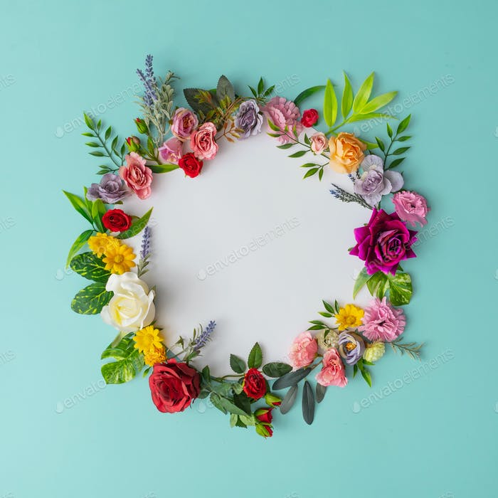 Spring wreath made of colorful flowers and leaves. Natural round frame layout with paper card.