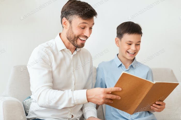 Father And Son Reading Book Sitting On Couch At Home