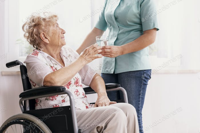 Professional nurse in a blue uniform gives a glass of water to an elderly woman in a wheelchair