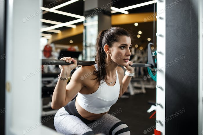 Athletic young girl dressed in sportswear squats with a barbell in the modern gym
