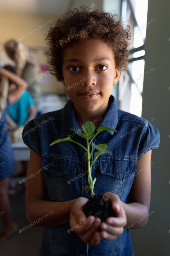 Schoolgirl standing holding a seedling plant in a jar of earth in an elementary school classroom