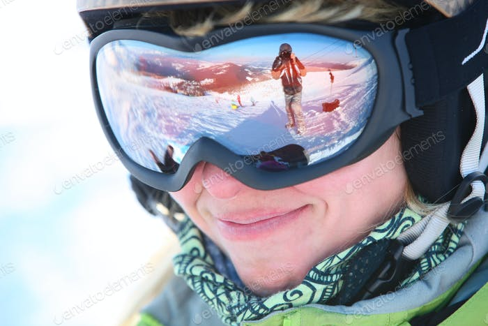 loseup portrait of a female skier standing on a skiing slope