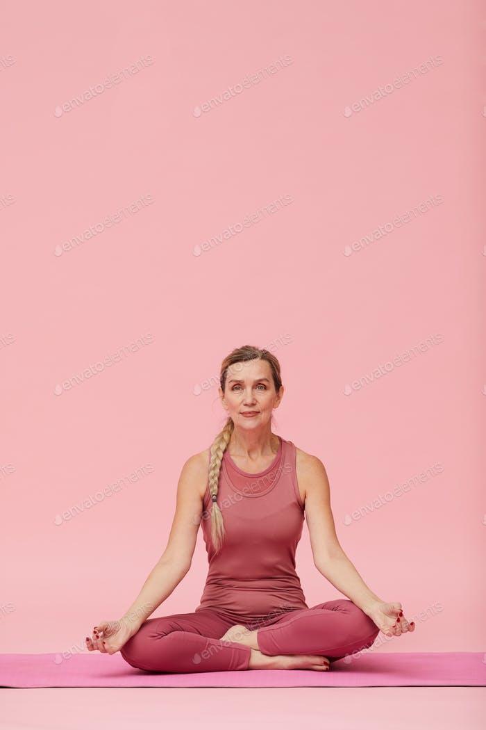 Mature Woman Sitting in Lotus Position on Pink