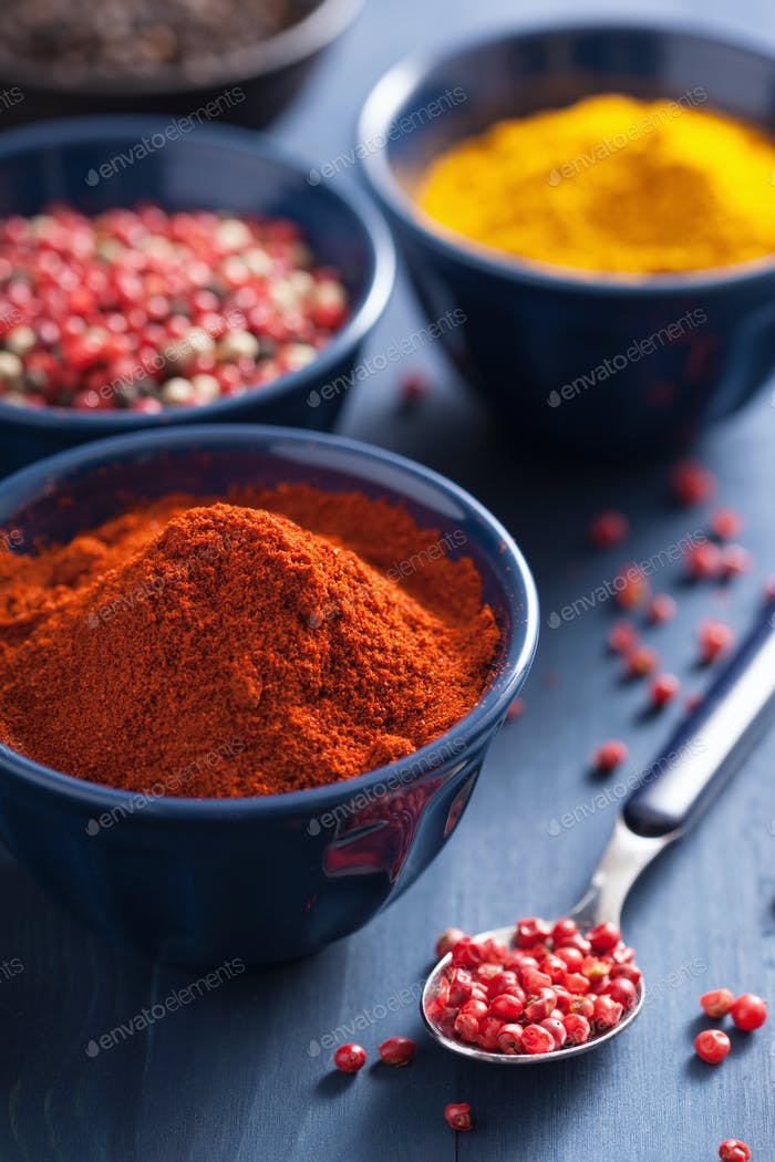 spices in bowls: curry, pink and black pepper, paprika powder