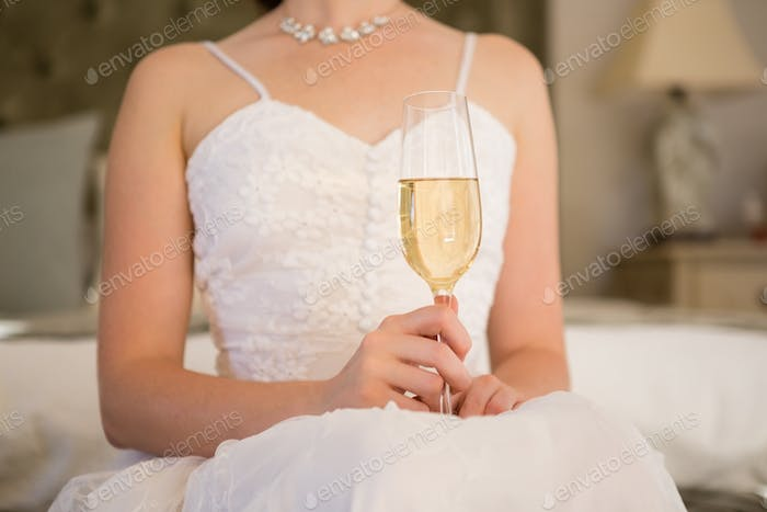 Midsection of bride holding champagne while sitting on bed