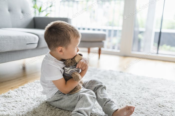 Cute child at home with his teddy bear