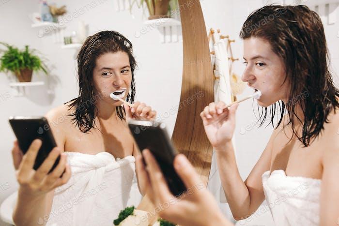 Junge glückliche Frau in weißem Handtuch Zähneputzen und auf Smartphone schauen