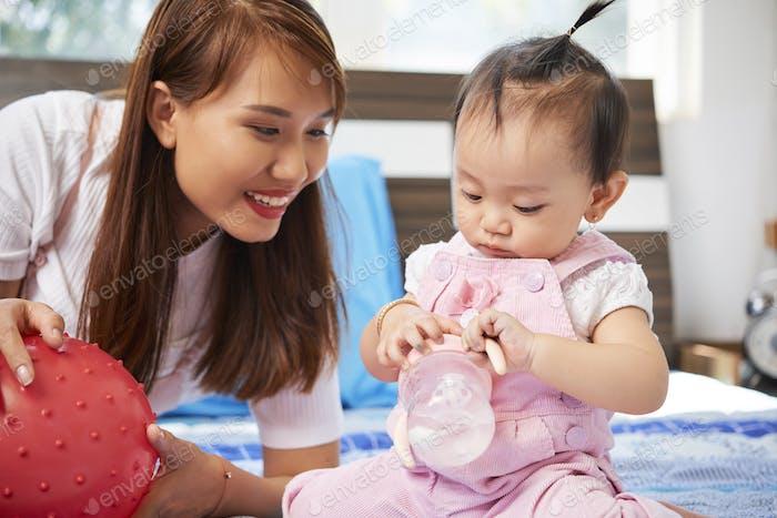 Baby spielt mit Nuckelflasche