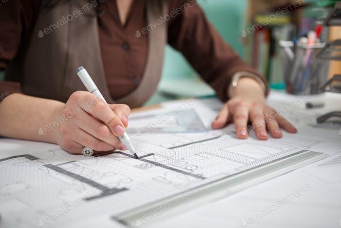 Nahaufnahme der Architektin Frau an ihrem Tisch Zeichnung auf Blaupausen