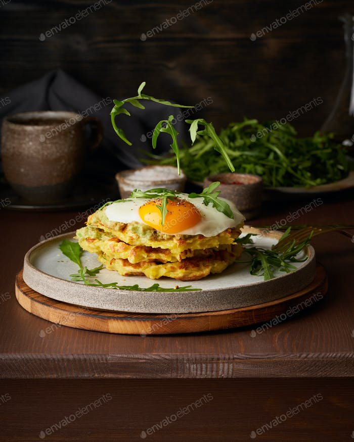 Homemade potato belgian waffles with fried egg, avocado sauce, flying arugula, mozzarella cheese.