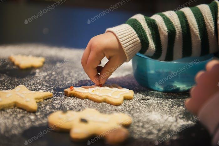 Ein Kind dekoriert Weihnachten Kekse.