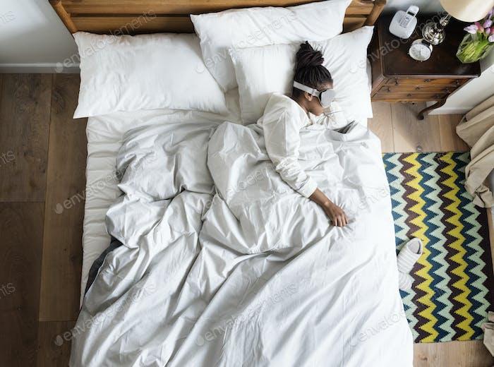 African American Frau auf Bett schlafen mit einer Augenabdeckung