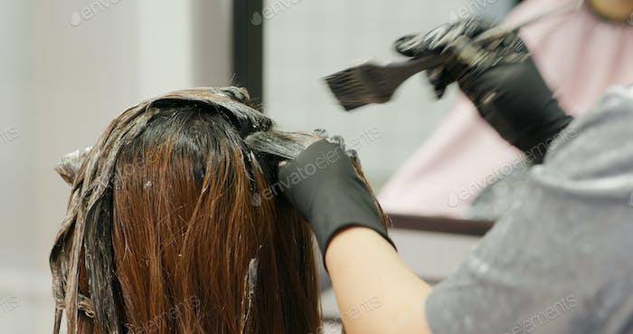 Woman undergo hair treatment at beauty salon, dye color on hair