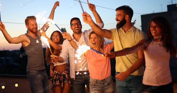Friends enjoying rooftop party with sparklers