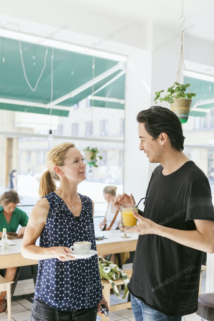 Mid adult man talking with woman in coffee shop