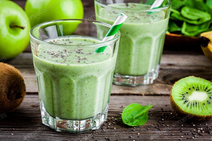 healthy green smoothie with apples, banana, kiwi, spinach and chia seeds in glass