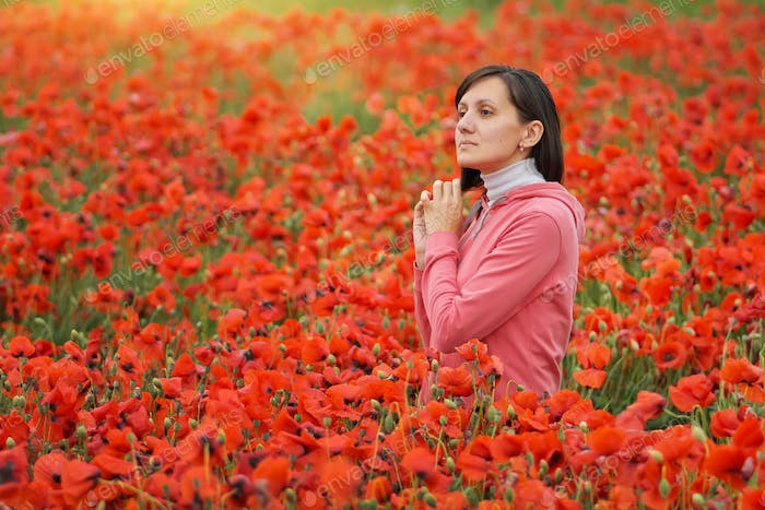 Cute young woman in big meadow of poppies.