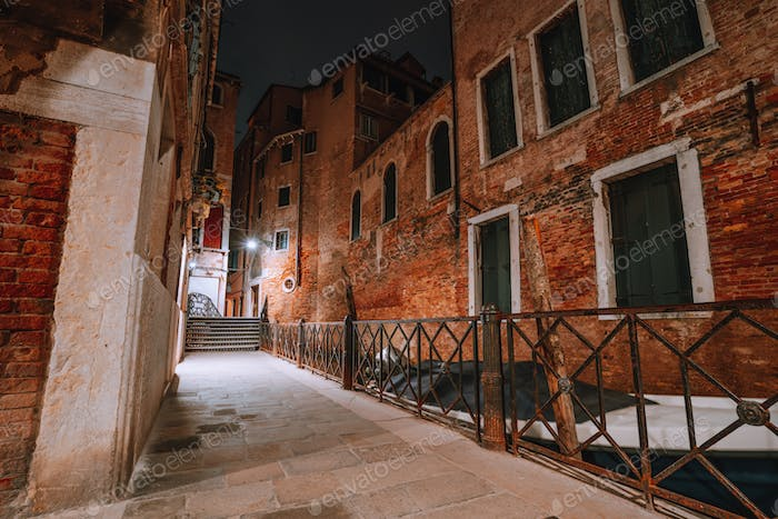 Gothic narrow streets with old red brick wall houses at night. Empty alleyways and bridge stairs in