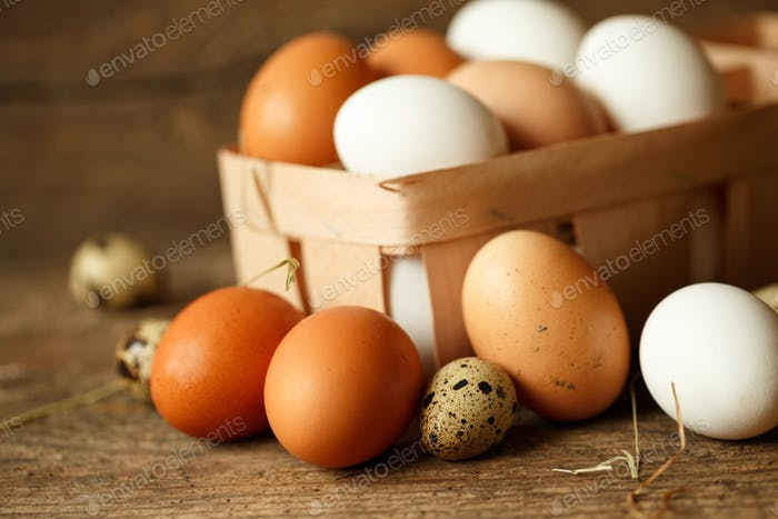 Fresh chicken and quail eggs on a wooden background
