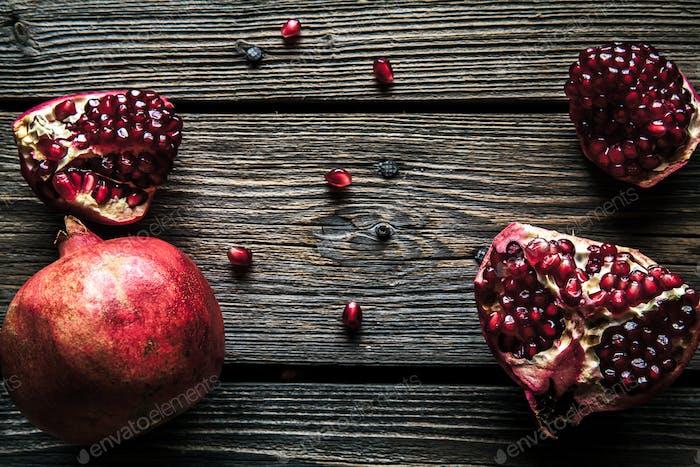Frischer roter Granatapfel und Grapefruit Auf einem hölzernen Hintergrund. Granatapfel in Platte auf Holzhintergrund